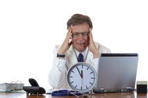 Gestresster Arzt mit Uhr vor sich hat Migräne wegen Zeitdruck